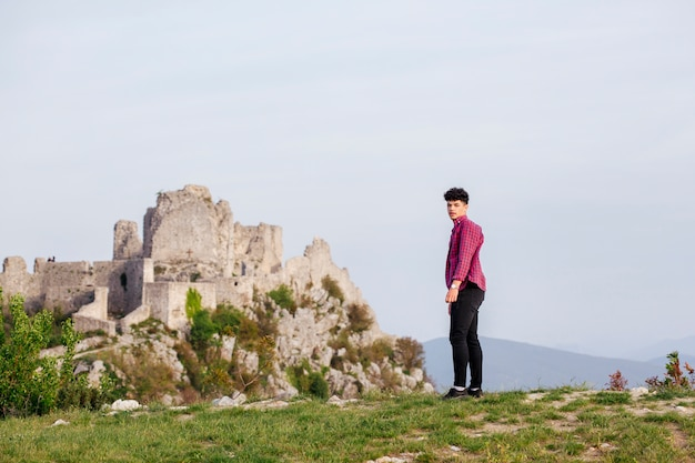 Encantadora jovem em pé perto de formação rochosa