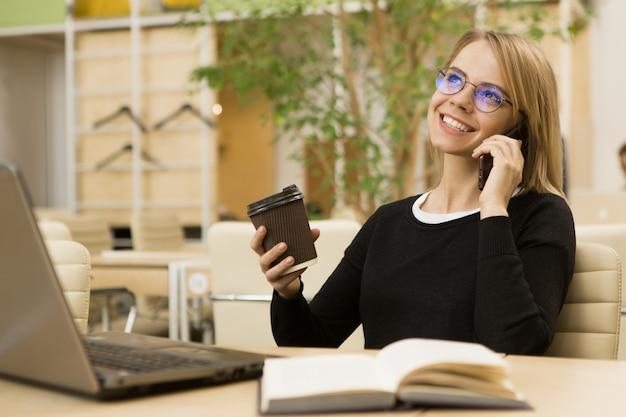 Encantadora jovem empresária trabalhando no escritório