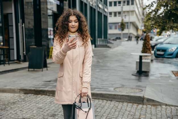 Encantadora jovem encaracolada com lindo sorriso fica na rua da cidade e usa smartphone e surpreende