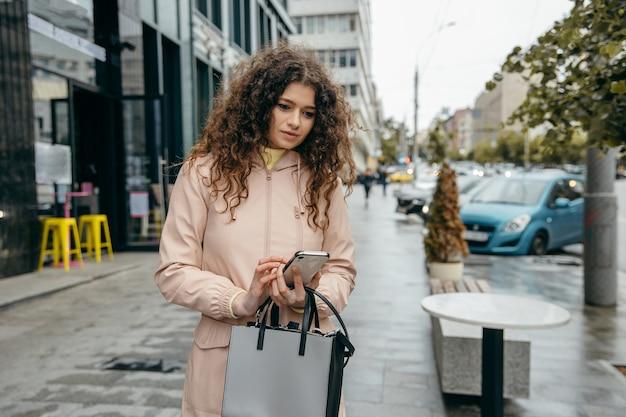 Encantadora jovem encaracolada com um lindo sorriso fica na rua da cidade e usa o smartphone