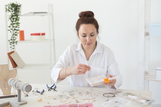 Encantadora jovem entusiasmada mulher caucasiana fazendo belas bijuterias exclusivas enquanto está sentado em sua mesa. conceito de hobby e trabalho prazeroso