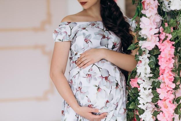 Encantadora jovem grávida posa em um estúdio com flores cor de rosa