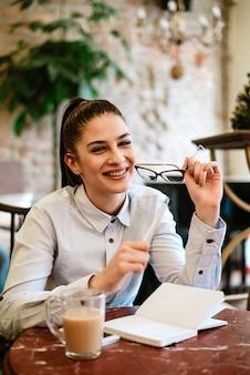 Encantadora jovem jornalista sentado no café. olhando para a câmera.