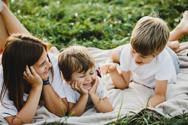 Encantadora jovem mãe se diverte com seus filhinhos deitado em um pl