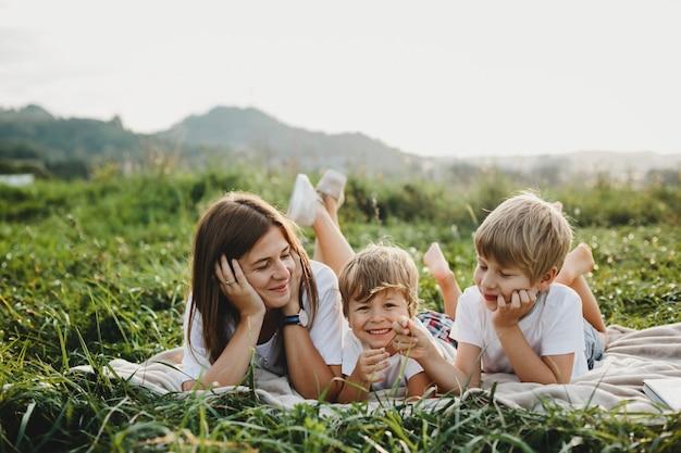 Encantadora jovem mãe se diverte com seus filhos pequenos mentindo