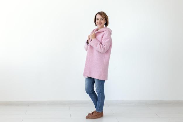 Encantadora jovem modelo feminino posando em um fundo branco com um casaco rosa de grife. o conceito de um design artesanal único. espaço publicitário, copyspace