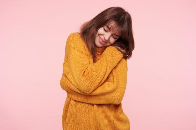 Encantadora jovem morena com maquiagem natural, abraçando-se com um sorriso gentil e mantendo os olhos fechados, em pé sobre a parede rosa