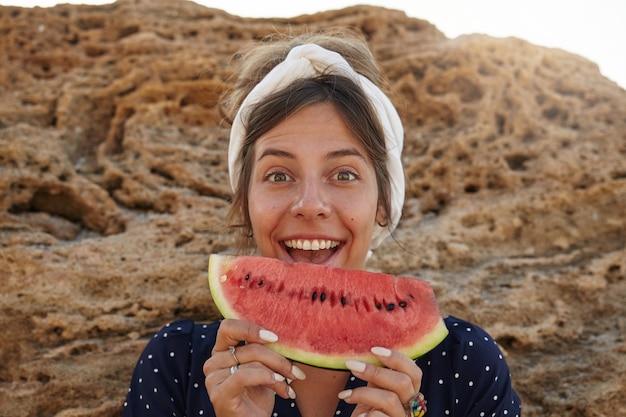 Encantadora jovem morena com uma bandana em pé sobre uma grande pedra e segurando um pedaço de melancia nas mãos, a testa contraída com a boca bem aberta