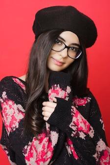 Encantadora jovem mulher com suéter de malha e boina preta, sorrindo e olhando para a câmera em pé sobre um fundo vermelho brilhante