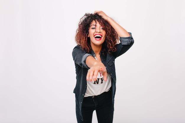 Encantadora jovem negra em jaqueta jeans, apontando com o dedo para frente. menina encaracolada refinada com sorriso animado, posando em pé de traje da moda.
