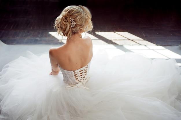 Encantadora jovem noiva vestido de noiva luxuoso. menina bonita de branco. fundo cinza. de volta