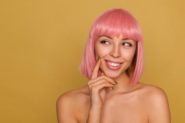 Encantadora jovem pensativa de cabelo rosa com maquiagem natural, mantendo o dedo indicador na bochecha e sorrindo alegremente enquanto fica de pé sobre a parede de mostarda