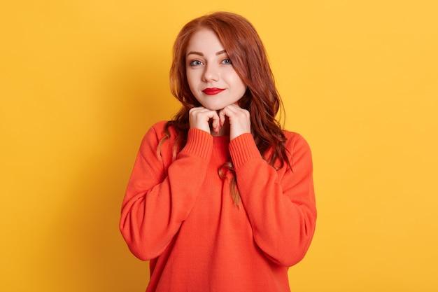 Encantadora jovem ruiva atraente com expressão fofa, olhando para a câmera, sorrindo alegremente, sentindo-se relaxada e feliz