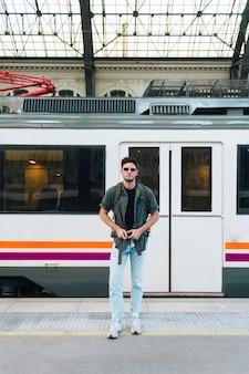 Encantadora jovem viajante ajustando alça de mochila em pé na plataforma