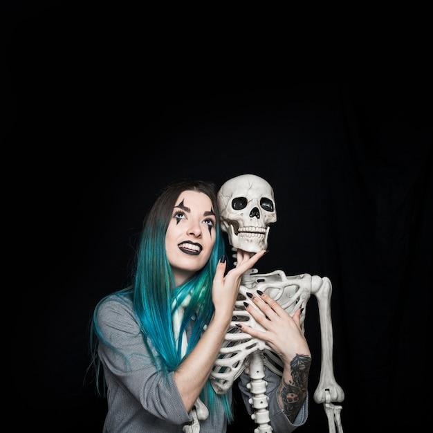 Encantadora menina abraçando o esqueleto de brinquedo