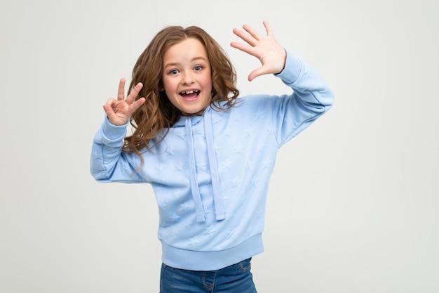 Encantadora menina adolescente com um capuz azul mostra oito dedos sobre um fundo cinza claro