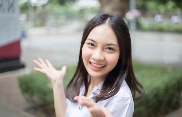 Encantadora menina asiática adolescente sorrindo em uniforme de estudante universitário