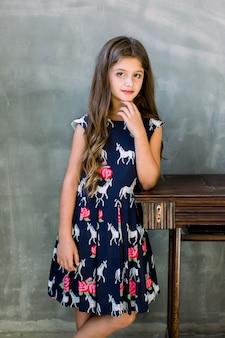 Encantadora menina bonitinha com longos cabelos morenos em vestido azul escuro, expressando isolado no pé da parede cinza, colocando as mãos em uma velha máquina de costura de madeira