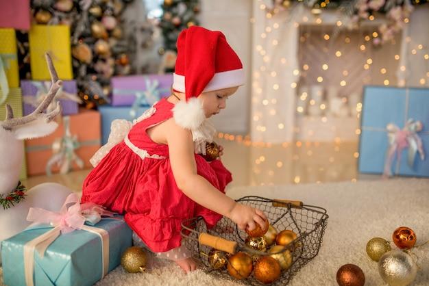 Encantadora menina brinca com brinquedos de árvore de natal