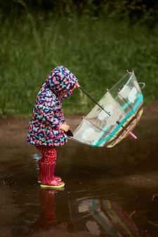 Encantadora menina com guarda-chuva tem diversão em pé na gumboots na piscina depois da chuva