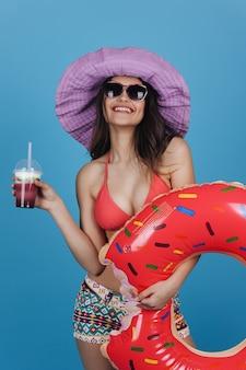Encantadora menina de chapéu e vestido de praia fica com um anel de natação coquetel e donut