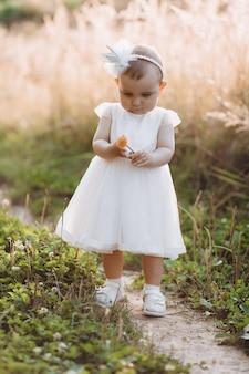 Encantadora menina de vestido branco caminha ao longo do caminho no campo