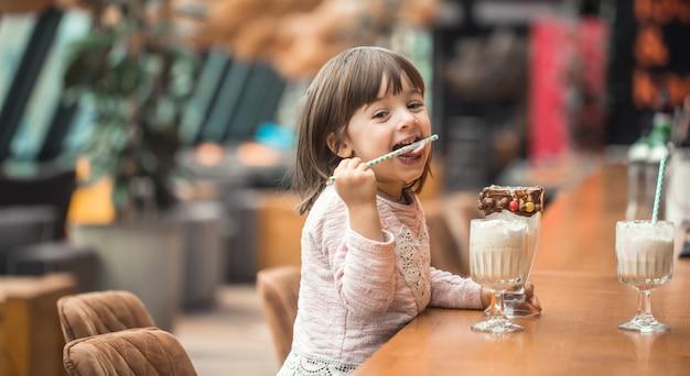 Encantadora menina engraçada bebe um batido