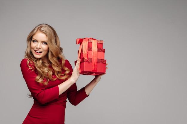 Encantadora menina feliz com caixas vermelhas com laço vermelho.