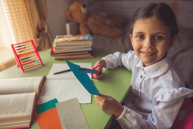 Encantadora menina na escola uniforme está cortando papel.