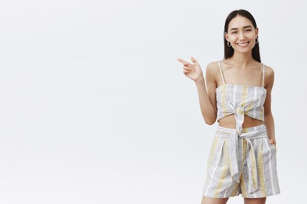 Encantadora modelo feminina asiática em roupa combinando, segurando a mão no bolso das camisas e apontando para a esquerda enquanto sorri alegre e amigável, mostrando o caminho para o bar, pedindo coquetel