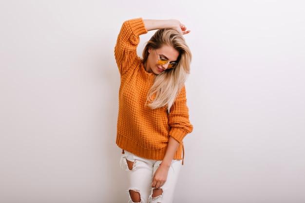 Encantadora modelo feminina em calças rasgadas da moda olhando para baixo enquanto posa no estúdio
