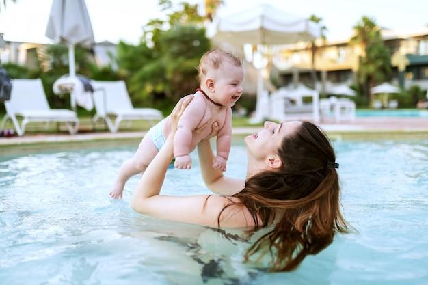 Encantadora morena caucasiana, levantando seu filho de 6 meses em pé na piscina. primeira vez no conceito de piscina.