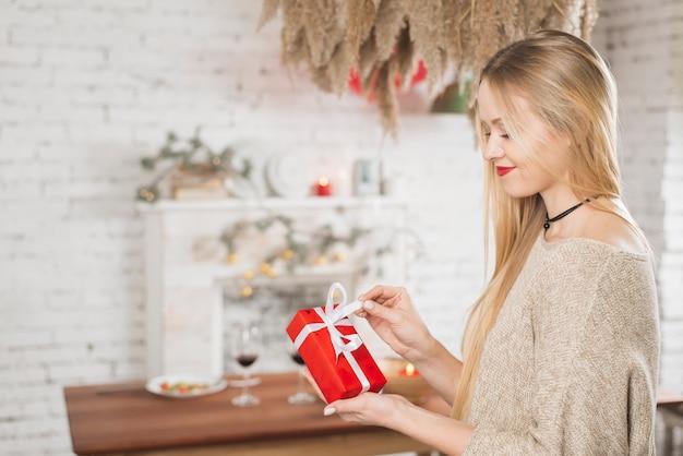Encantadora mulher abrindo a caixa de presente