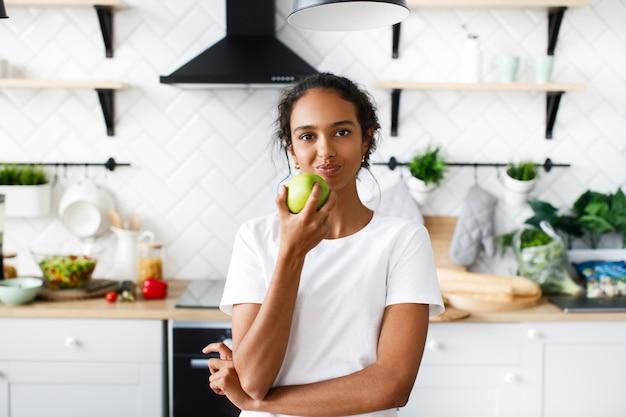 Encantadora mulher africana está comendo uma maçã verde na cozinha