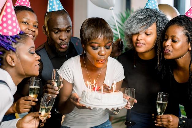 Encantadora mulher africana soprando velas no bolo de aniversário depois de fazer o seu desejo na festa