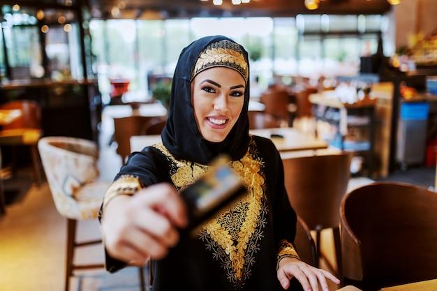 Encantadora mulher árabe positiva com sorriso lindo vestido com roupas tradicionais, sentado no café
