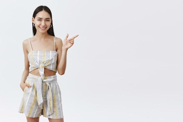 Encantadora mulher asiática de cabelos escuros em um top moderno, apontando para a direita com o dedo indicador e sorrindo enquanto ajuda a encontrar o caminho para o banheiro por cima da parede cinza