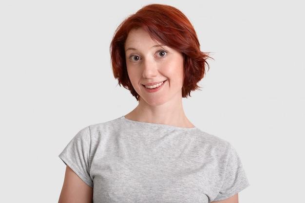 Encantadora mulher attactive com penteado curto, tem um sorriso largo, vestido com camiseta cinza casual