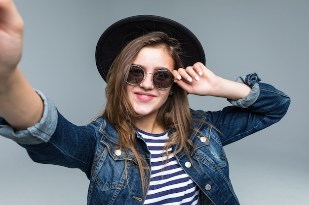 Encantadora mulher bonita no chapéu preto e óculos de sol tirar selfie de mãos no fundo cinza