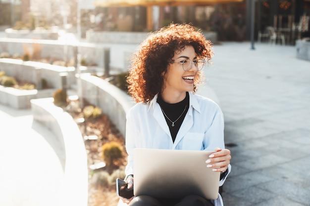 Encantadora mulher caucasiana de cabelos cacheados está sentada na escada de pedra e trabalhando com seu computador enquanto usa óculos e desvia o olhar