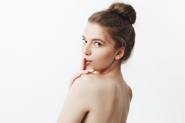 Encantadora mulher caucasiana jovem sexy bonita com cabelo castanho no penteado elegante e corpo nu, segurando o dedo na frente dos lábios em três aspas