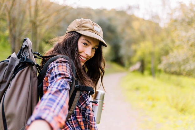Encantadora mulher com garrafa térmica oferecendo reboque andar com ela