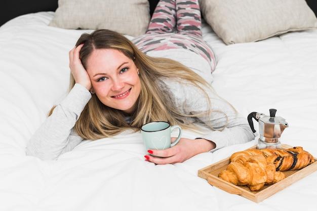 Encantadora mulher deitada na cama perto de comida de café da manhã