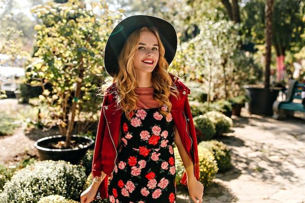 Encantadora mulher encaracolada com chapéu de aba larga e vestido com rosas com sorriso posando no parque.