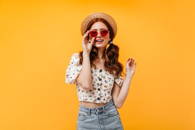 Encantadora mulher encaracolada em elegante blusa cortada e saia jeans usa óculos de sol vermelhos. mulher no velejador olha para a câmera em fundo laranja.