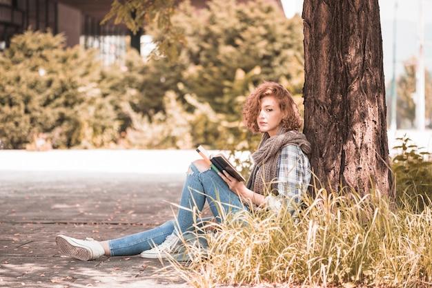 Encantadora mulher encostado na árvore e segurando o livro no parque