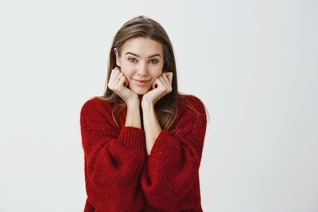 Encantadora mulher europeia flertando com cabelo loiro lindo suéter vermelho solto, inclinando a cabeça nas mãos e olhando com um sorriso fofo positivo, ouvindo uma história interessante