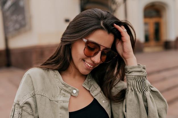 Encantadora mulher europeia tímida com cabelo escuro, usando óculos escuros e jaqueta andando pela cidade em um bom dia de sol