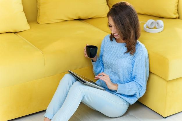 Encantadora mulher exuberante segurando seu ipad nas mãos, sentada no chão perto do sofá verde claro e desfrutando de café na xícara na cozinha contemporânea