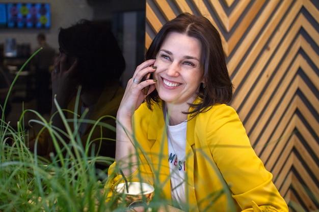 Encantadora mulher falando no celular enquanto relaxa no café